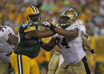 GREEN BAY, WI - SEPTEMBER 08: B.J. Raji #90 of the Green Bay Packers rushes against Jermon Bushrod #74 of the New Orleans Saints during the NFL opening season game at Lambeau Field on September 8, 2011 in Green Bay, Wisconsin. The Packers defeated the Sai