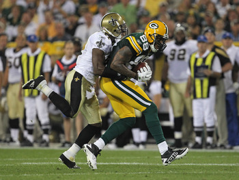 GREEN BAY, WI - SEPTEMBER 08:  Tracy Porter #22 of the New Orleans Saints tackles Jermichael Finley #88 of the Green Bay Packers during the NFL opening season game at Lambeau Field on September 8, 2011 in Green Bay, Wisconsin. The Packers defeated the Sai