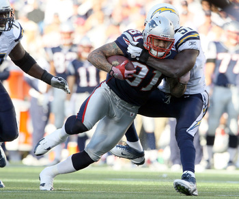FOXBORO, MA - SEPTEMBER 18:   Aaron Hernandez #81 of the New England Patriots is tackled by Takeo Spikes #51 of the San Diego Chargers on September 18, 2011 at Gillette Stadium in Foxboro, Massachusetts.  (Photo by Elsa/Getty Images)