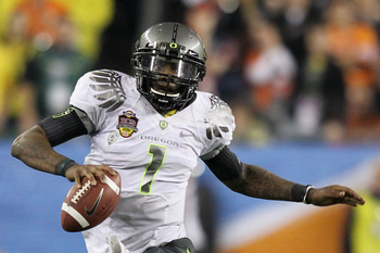 GLENDALE, AZ - JANUARY 10:  Darron Thomas #1 of the Oregon Ducks scrambles against Mike McNeil #26 of the Auburn Tigers during the Tostitos BCS National Championship Game at University of Phoenix Stadium on January 10, 2011 in Glendale, Arizona.  (Photo b
