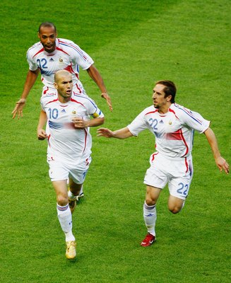 BERLIN - JULY 09:  Zinedine Zidane of France celebrates with team mates Thierry Henry (L) and Frank Ribery (R) after scoring the opening goal  from the penalty spot during the FIFA World Cup Germany 2006 Final match between Italy and France at the Olympic
