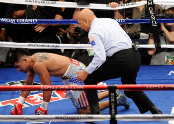 LAS VEGAS, NV - SEPTEMBER 17:  (R) Referee Joe Cortez counts as (C) Victor Ortiz is knocked out by Floyd Mayweather Jr. during their WBC welterweight title fight at the MGM Grand Garden Arena on September 17, 2011 in Las Vegas, Nevada.  (Photo by Ethan Mi