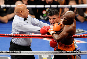 LAS VEGAS, NV - SEPTEMBER 17:  Referee Joe Cortez pulls Victor Ortiz off Floyd Mayweather Jr. as Ortiz is called for a minus point for a head-butt in the fourth round during their WBC welterweight title fight at the MGM Grand Garden Arena on September 17,