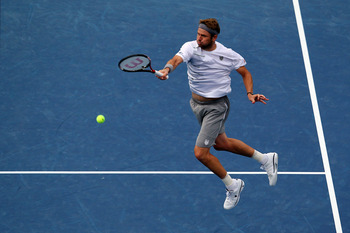 NEW YORK, NY - SEPTEMBER 05:  Mardy Fish of the United States returns a shot against Jo-Wilfried Tsonga of France during Day Eight of the 2011 US Open at the USTA Billie Jean King National Tennis Center on September 5, 2011 in the Flushing neighborhood of