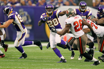 MINNEAPOLIS, MN - SEPTEMBER 18:  Adrian Peterson #28 of the Minnesota Vikings carries the ball for a gain while  Sean Jones #26 of the Tampa Bay Buccaneers applies pressure at the Hubert H. Humphrey Metrodome on September 18, 2011 in Minneapolis, Minnesot