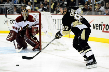 PITTSBURGH - DECEMBER 20:  Sidney Crosby #87 of the Pittsburgh Penguins passes the puck in front of Jason LaBarbera #1 of the Phoenix Coyotes during the game on December 20, 2010 in Pittsburgh, Pennsylvania.  (Photo by Karl Walter/Getty Images)