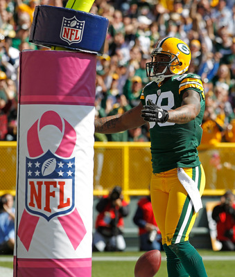 GREEN BAY, WI - OCTOBER 03: Jermichael Finley #88 of the Green Bay Packers celebrates a touchdown catch against the Detroit Lions in front of a goal post wrapped with a breast cancer awarness pad at Lambeau Field on October 3, 2010 in Green Bay, Wisconsin
