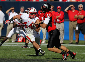 CHICAGO, IL - SEPTEMBER 17:  Chris Borland #44 of the Wisconsin Badgers chases Chandler Harnish #12 of the Northern Illinois Huskies at Soldier Field on September 17, 2011 in Chicago, Illinois. Wisconsin defeated Northern Illinois 49-7.  (Photo by Jonatha