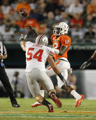 MIAMI, FL - SEPTEMBER 17: Jacory Harris #12 of the Miami Hurricanes gets the pass away while being pressured by John Simon #54 of the Ohio State Buckeyes on September 17, 2011 at Sun Life Stadium in Miami, Florida. The Hurricanes defeated the Buckeyes 24-