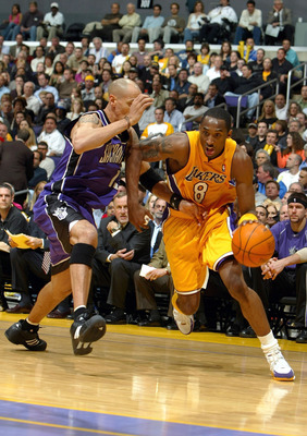 LOS ANGELES - MARCH 24:  Kobe Bryant #8 of the Los Angeles Lakers drives from the outside defended by Doug Christie #13 of the Sacramento Kings during the game at Staples Center on March 24, 2004 in Los Angeles, California.  NOTE TO USER: User expressly a
