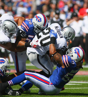 ORCHARD PARK, NY - SEPTEMBER 18:  Darren McFadden #20 of the Oakland Raiders is tackled by  Nick Barnett #50 and  Shawne Merriman #56 of the Buffalo Bills at Ralph Wilson Stadium on September 18, 2011 in Orchard Park, New York.  (Photo by Rick Stewart/Get