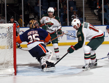 UNIONDALE, NY - MARCH 02: John Madden #11 of the Minnesota Wild scores a goal against Al Montoya #35 of the New York Islanders at the Nassau Coliseum on March 2, 2011 in Uniondale, New York. The Islanders defeated the Wild 4-1.  (Photo by Bruce Bennett/Ge