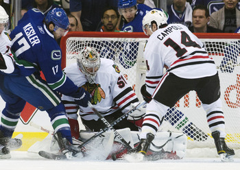 VANCOUVER, CANADA - APRIL 26: Ryan Kesler #17 of the Vancouver Canucks tips the puck towards goalie Corey Crawford #50 of the Chicago Blackhawks while being watched by Chris Campoli #14 of the Chicago Blackhawks during the first period in Game Seven of th