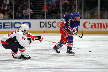 NEW YORK, NY - APRIL 17: Bryan McCabe #28 of the New York Rangers attempts a shot against Boyd Gordon #15 of the Washington Capitals in Game Three of the Eastern Conference Quarterfinals during the 2011 NHL Stanley Cup Playoffs at Madison Square Garden on