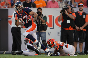 DENVER, CO - SEPTEMBER 18:  Wide receiver Eric Decker #87 of the Denver Broncos eludes the defense of Chris Crocker #42 of the Cincinnati Bengals and Nate Clements #22 of the Cincinnati Bengals for a 52 yard touchdown reception in the fourth quarter at In