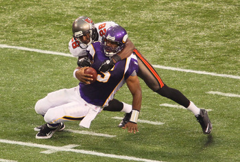 MINNEAPOLIS, MN - SEPTEMBER 18:    Donovan McNabb #5 of the Minnesota Vikings gets sacked by Sean Jones #26 of the Tampa Bay Buccaneers at the Hubert H. Humphrey Metrodome on September 18, 2011 in Minneapolis, Minnesota.  (Photo by Adam Bettcher /Getty Im