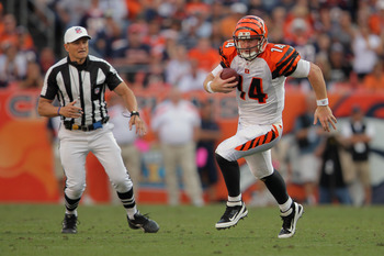 DENVER, CO - SEPTEMBER 18:  Quarterback Andy Dalton #14 of the Cincinnati Bengals scrambles with the ball against the Denver Broncos as referee Ed Hochuli #85 oversees the action at Sports Authority Field at Mile High on September 18, 2011 in Denver, Colo