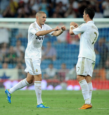 MADRID, SPAIN - SEPTEMBER 10:  Cristiano Ronaldo (R) of Real Madrid salutes Karim Benzema after Benzema was substituted late in the second half of the La Liga match bewteen Real Madrid and Getafe at Estadio Santiago Bernabeu on September 10, 2011 in Madri