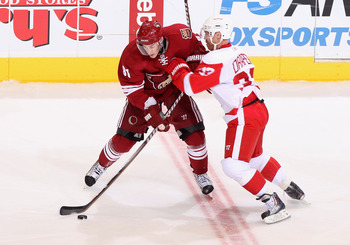 GLENDALE, AZ - APRIL 20:  Kyle Turris #91 of the Phoenix Coyotes skates with the puck under pressure from Kris Draper #33 of the Detroit Red Wings in Game Four of the Western Conference Quarterfinals during the 2011 NHL Stanley Cup Playoffs at Jobing.com