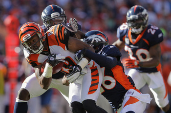 DENVER, CO - SEPTEMBER 18:  Wide receiver Jerome Simpson #89 of the Cincinnati Bengals makes a 31 yard pass reception as Cassius Vaughn #41 and Rahim Moore #26 of the Denver Broncos make the tackle in the third quarter at Invesco Field at Mile High on Sep