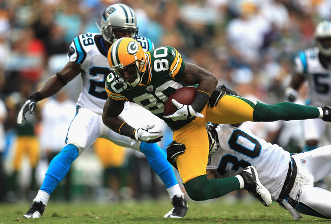 CHARLOTTE, NC - SEPTEMBER 18:   Donald Driver #80 of the Green Bay Packers is tackled by Charles Godfrey #30 of the Carolina Panthers during their game at Bank of America Stadium on September 18, 2011 in Charlotte, North Carolina.  (Photo by Streeter Leck