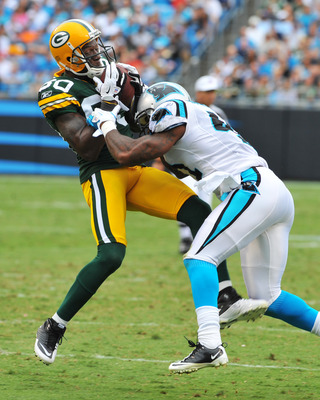 CHARLOTTE, NC - SEPTEMBER 18:  Cornerback Captain Munnerlyn #41 of the Carolina Panthers tackles wide receiver Donald Driver #80 of the Green Bay Packers September 18, 2011 at Bank of America Stadium in Charlotte, North Carolina.  (Photo by Al Messerschmi