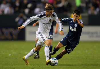 CARSON, CA - SEPTEMBER 17:  David Beckham #23 of the Los Angeles Galaxy plays the ball past Shea Salinas #22 of the Vancouver Whitecaps in the first half during the MLS match at The Home Depot Center on September 17, 2011 in Carson, California. The Galaxy