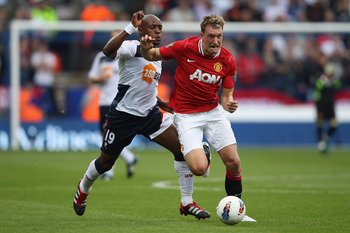 BOLTON, ENGLAND - SEPTEMBER 10: Phil Jones (R) of Manchester United tracked by Nigel Reo-Coker of Bolton Wanderers during the Barclays Premier League at the Reebok Stadium on September 10, 2011 in Bolton, England.  (Photo by Michael Steele/Getty Images)
