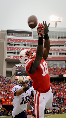 LINCOLN, NE - SEPTEMBER 17: Quincy Enunwa #18 of the Nebraska Cornhuskers reaches for a pass over Gregory Ducre #18 of the Washington Huskies during their game at Memorial Stadium September 17, 2011 in Lincoln, Nebraska. Nebraska won 51-38.  (Photo by Eri