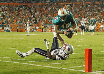 MIAMI GARDENS, FL - SEPTEMBER 12:   Brandon Marshall #19 of the Miami Dolphins scores a touchdown over  Devin McCourty #32 of the New England Patriots during a game  at Sun Life Stadium on September 12, 2011 in Miami Gardens, Florida.  (Photo by Mike Ehrm