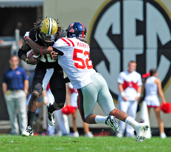 NASHVILLE, TN - SEPTEMBER 17:  Quarterback Larry Smith #10 of the Vanderbilt Commodores is sacked by Mike Marry #52 of the Ole Miss Rebels at Vanderbilt Stadium on September 17, 2011 in Nashville, Tennessee.  (Photo by Grant Halverson/Getty Images)