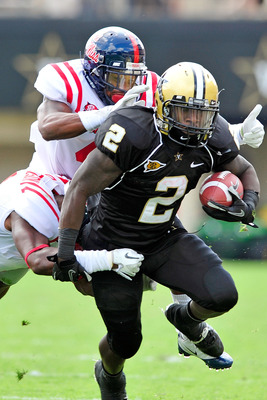 NASHVILLE, TN - SEPTEMBER 17:  Marcus Temple #4 and Damien Jackson #1 of the Ole Miss Rebels tackle Zac Stacy #2 of the Vanderbilt Commodores at Vanderbilt Stadium on September 17, 2011 in Nashville, Tennessee.  (Photo by Grant Halverson/Getty Images)