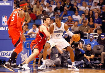 ORLANDO, FL - APRIL 19:  Dwight Howard #12 of the Orlando Magic drives as Zaza Pachulia #27 of the Atlanta Hawks defends during Game Two of the Eastern Conference Quarterfinals of the 2011 NBA Playoffs on April 19, 2011 at the Amway Arena in Orlando, Flor