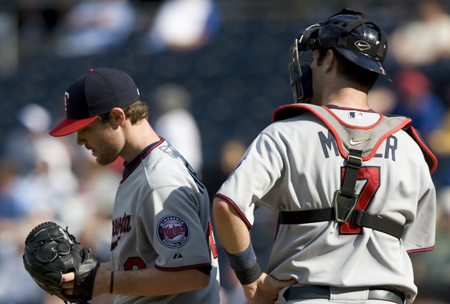 KANSAS CITY, MO - SEPTEMBER 14:  Joe Mauer #7 of the Minnesota Twins talks with starting pitcher Liam Hendriks in the fourth inning during a game against the Kansas City Royals at Kauffman Stadium on September 14, 2011 in Kansas City, Missouri. (Photo by