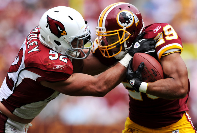 LANDOVER, MD - SEPTEMBER 18: Running back Roy Helu #29 of the Washington Redskins is forced out of bounds by linebacker Stewart Bradley #52 of the Arizona Cardinals during the second half at FedExField on September 18, 2011 in Landover, Maryland. The Wash