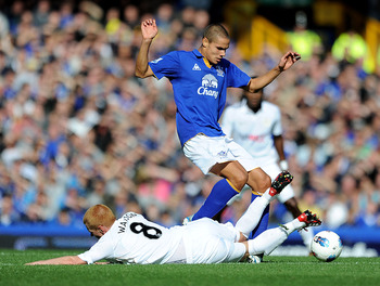 LIVERPOOL, ENGLAND - SEPTEMBER 17:   Jack Rodwell of Everton tangles with Ben Watson of Wigan Athletic during the Barclays Premier League match between Everton and Wigan Athletic at Goodison Park on September 17, 2011 in Liverpool, England. (Photo by Chri