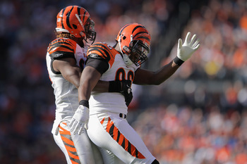 DENVER, CO - SEPTEMBER 18:  Michael Johnson #93 of the Cincinnati Bengals celebrates with teammate Carlos Dunlap #96 of the Cincinnati Bengals after causing quarterback Kyle Orton #8 of the Denver Broncos to fumble and turnover the ball at Sports Authorit