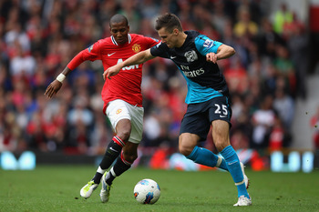MANCHESTER, ENGLAND - AUGUST 28:  Ashley Young of Manchester United and Carl Jenkinson of Arsenal battle for the ball during the Barclays Premier League match between Manchester United and Arsenal at Old Trafford on August 28, 2011 in Manchester, England.