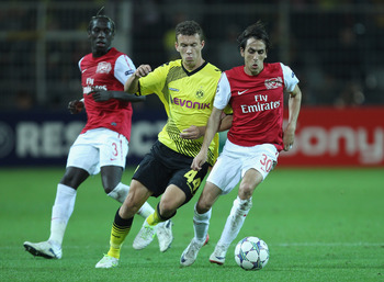 DORTMUND, GERMANY - SEPTEMBER 13:  Yossi Benayoun of Arsenal is tackled by Ivan Perisic of Borussia Dortmund during the UEFA Champions League Group F match between Borussia Dortmund and Arsenal FC at Signal Iduna Park on September 13, 2011 in Dortmund, Ge
