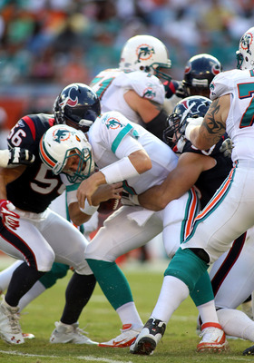MIAMI GARDENS, FL - SEPTEMBER 18: Linebackers Brian Cushing #56 and Connor Barwin #98 of the Houston Texans sack Quarterback Chad Henne #7 of  the Miami Dolphins at Sun Life Stadium on September 18, 2011 in Miami Gardens, Florida.  (Photo by Marc Serota/G