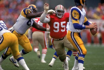 SAN FRANCISCO - NOVEMBER 25:  Defensive tackle Michael Carter #95 of the San Francisco 49ers rushes the quarterback Jim Everett #11 of the Los Angeles Rams as he gets past offensive guard Duval Love #67 during a game at Candlestick Park on November 25, 19