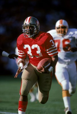 SAN FRANCISCO - NOVEMBER 18:  Running back Roger Craig #33 of the San Francisco 49ers breaks away from the Tampa Bay Buccaneers defense during a game at Candlestick Park on November 18, 1990 in San Francisco, California.  The 49ers won 31-7.  (Photo by Ge