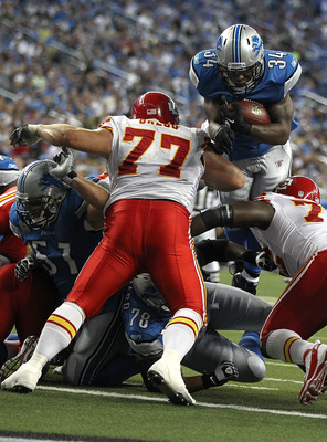 DETROIT, MI - SEPTEMBER 18:  Keiland Williams #34 of the Detroit Lions leaps into the air and into the end zone for a touch down as Kelly Gregg #77 of the Kansas City Chiefs defends during a NFL game at Ford Field on September 18, 2011 in Detroit, Michiga