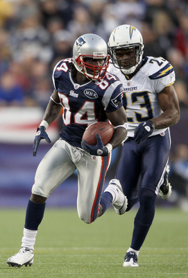 FOXBORO, MA - SEPTEMBER 18:  Deion Branch #84 of the New England Patriots carries the ball as  Quentin Jammer #23 of the San Diego Chargers defends on September 18, 2011 at Gillette Stadium in Foxboro, Massachusetts.  (Photo by Elsa/Getty Images)