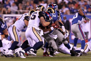 EAST RUTHERFORD, NJ - SEPTEMBER 19:  Brandon Jacobs #27 of the New York Giants has his facemask grabbed by James Laurinaitis #55 of the St. Louis Rams as he runs the ball in the second half at MetLife Stadium on September 19, 2011 in East Rutherford, New