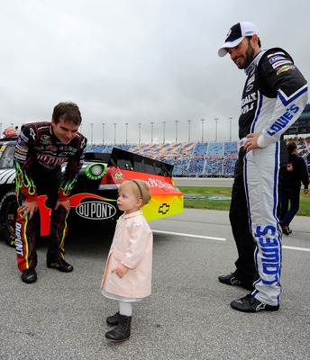 JOLIET, IL - SEPTEMBER 19:  Jeff Gordon (L), driver of the #24 DuPont Chevrolet, and Jimmie Johnson (R), driver of the #48 Lowe's/Kobalt Tools Chevrolet, look at Jimmie's daughter Genevieve Marie (C) on the grid prior to the NASCAR Sprint Cup Series GEICO