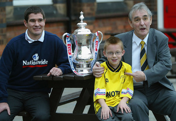 BURTON, ENGLAND - DECEMBER 4:  Nigel Clough and  father Brian pose with a young Burton Albion supporter and the FA Cup at the Holy Trinity Primary School on December 4, 2003 in Burton-on-Trent, England.  Burton Albion will play Hartlepool in the FA Cup on