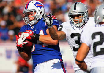 ORCHARD PARK, NY - SEPTEMBER 18:  Scott Chandler #84 of the Buffalo Bills scores Buffalo's fourth touchdown on a catch against Tyvon Branch #33 of the Oakland Raiders at Ralph Wilson Stadium on September 18, 2011 in Orchard Park, New York. Buffalo won 38-