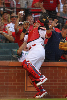 ST. LOUIS, MO - JULY 27: Yadier Molina #4 of the St. Louis Cardinals catches a foul ball against the netting behind home plate against the Houston Astros at Busch Stadium on July 27, 2011 in St. Louis, Missouri.  (Photo by Dilip Vishwanat/Getty Images)
