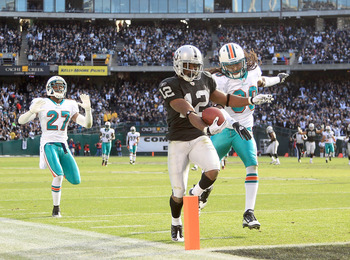 OAKLAND, CA - NOVEMBER 28:  Jacoby Ford #12 of the Oakland Raiders runs past Benny Sapp #27 and Chris Clemons #30 of the Miami Dolphins to score a touchdown at Oakland-Alameda County Coliseum on November 28, 2010 in Oakland, California.  (Photo by Ezra Sh